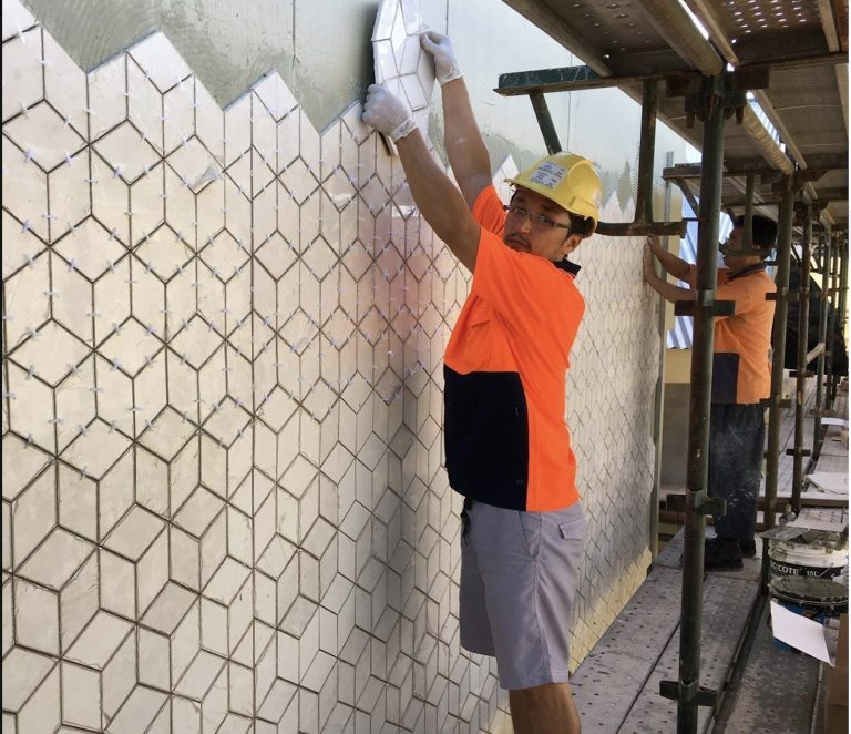 Man placing a tile in wall.