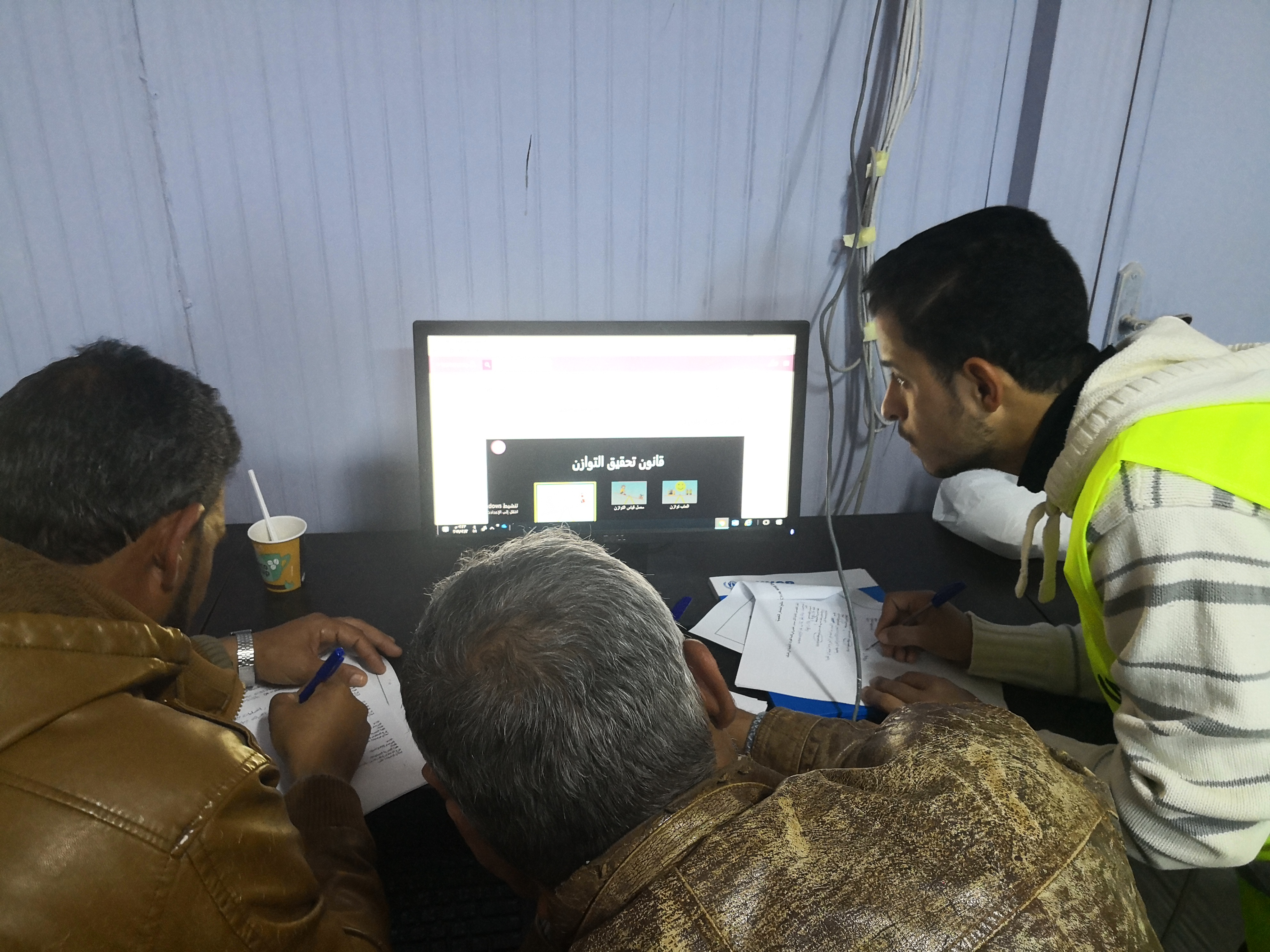 Refugees in front of computer using the education platform