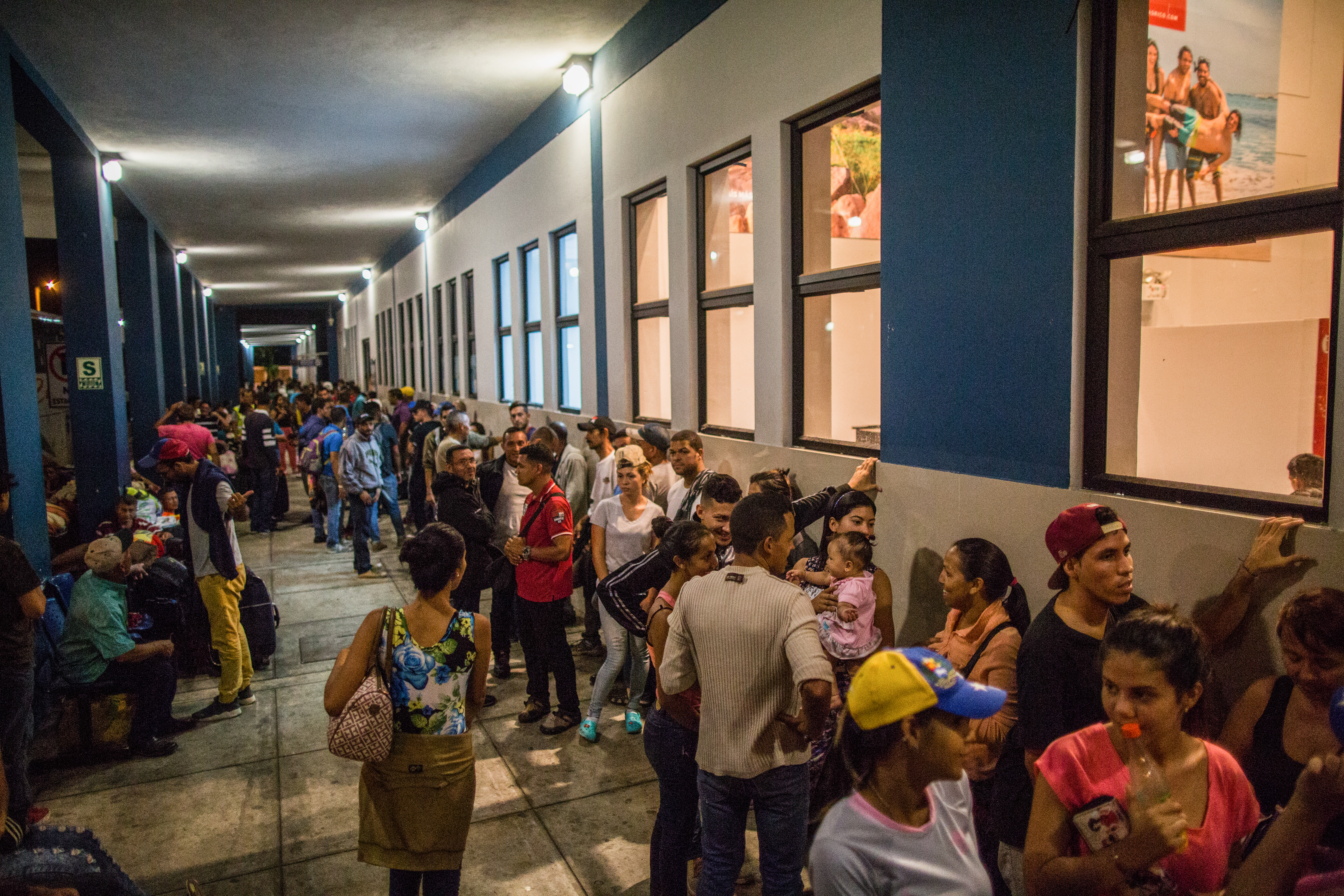 Venezuelans waiting and queuing inside a building.