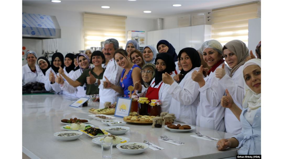 A big group of women in aprons faces the camera
