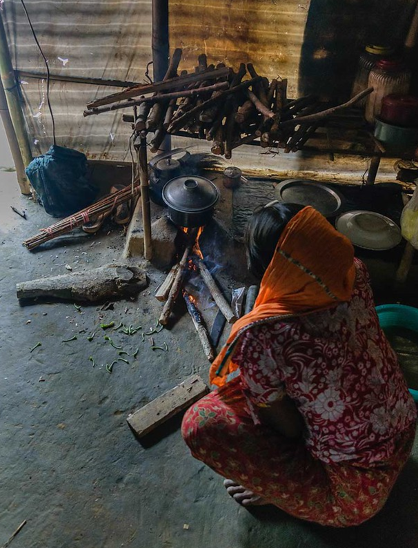 Woman seated on the floor in front of a cooker with firewood.