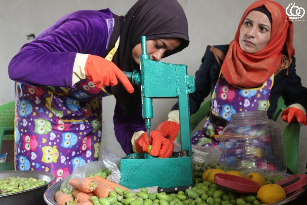 Two women are pitting olives