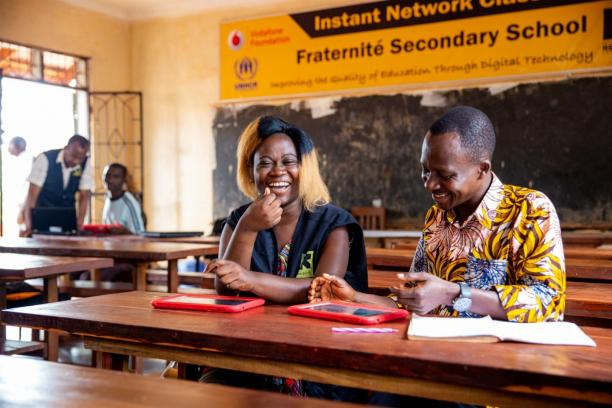 Volunteers sitting at a desk in a classroom looking at tablets and laughing