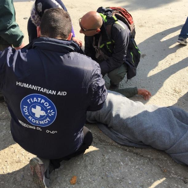 Two people from the MdM Greece medical staff are assisting a refugee that fainted and is lying on the ground in Lesvos