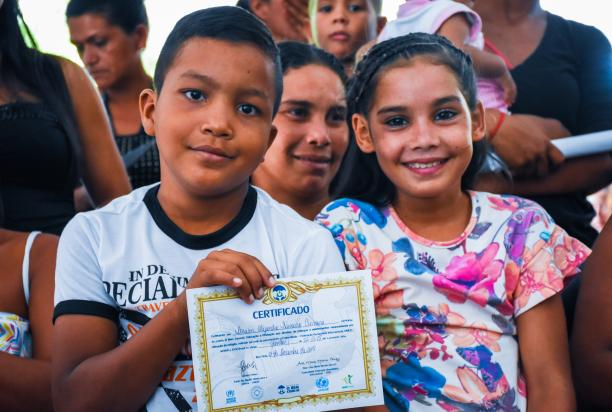 Children holding a certificate for participating in the project.