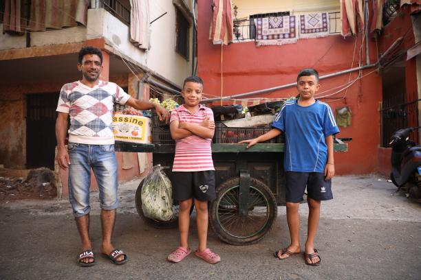 Two boys stand with their father in front of vegetable cart