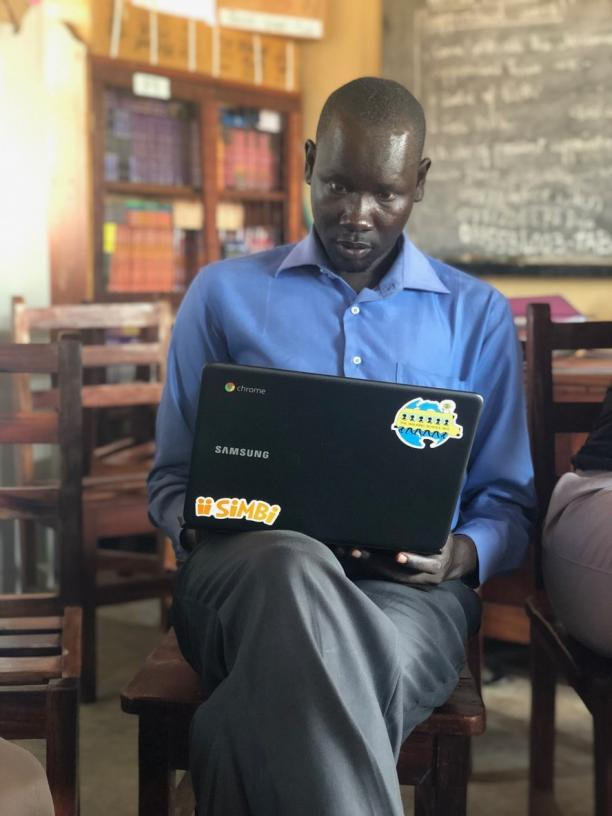 Man looking sitting on a chair looking at a laptop