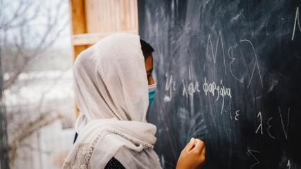 A person wearing a mask writes on a black board