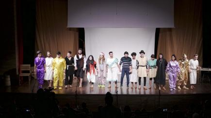A big group of actors in costumes stand on stage, holding hands and facing the audience
