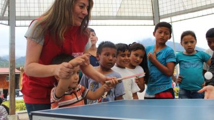 A woman standing near a tennis table teaching children to play