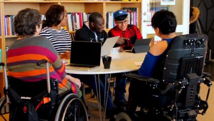 A group of people sitting together at a table, some are in wheelchairs.