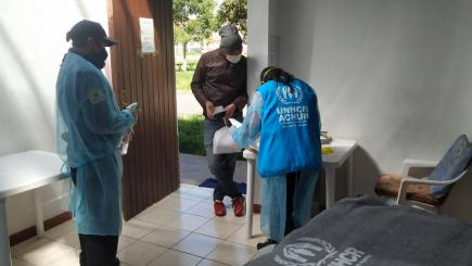 UNHCR staff distributing blankets to man.