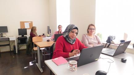 Women with laptops in a classroom.