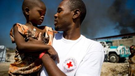 Humanitarian worker with refugee child on his arm