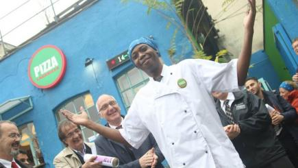 A chef standing with his hands up and smiling, while others clap.