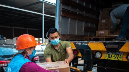 Man and woman unload cardboard crates from truck