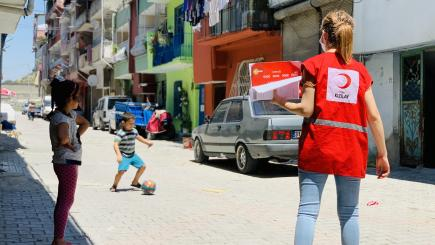 Two children play ball in the street with a red crescent worker