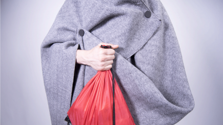Torso of a person wearing an adapted UNHCR blanket and holding a red bag