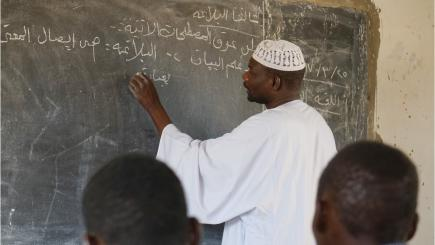 In the forefront to people sit back to the camera, in the background a man is writing on a blackboard