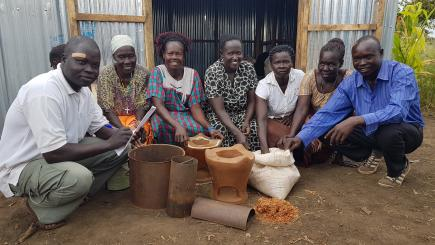 A group of people show a range of cooking pots