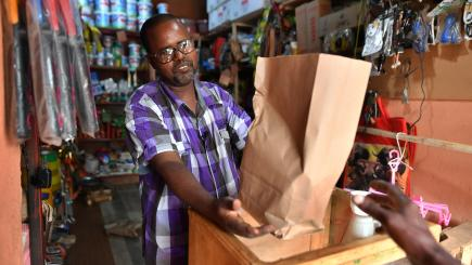 A man in a shop hands over goods in a brown paper bag.