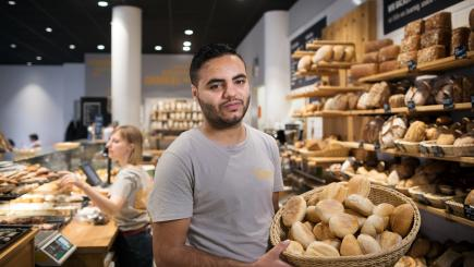 A man in a bakery displays a basket of bread.