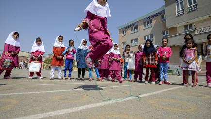 A girl jumps high over a skipping rope while others watch around.
