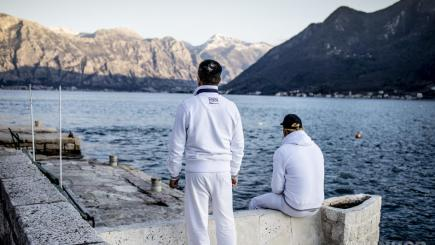 Two men sit with their backs to the camera. They are looking at a lake with mountains in the background