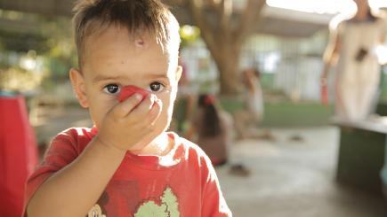 A child looks at the camera, has one hand in front of their face