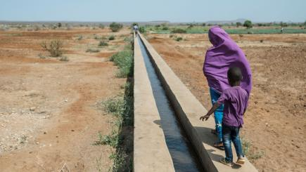 A girl and a boy walk along a canal in an irrigated farming land in Melkadida, Ethiopia.