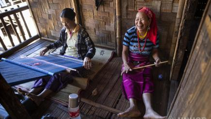 Two women sit together weaving