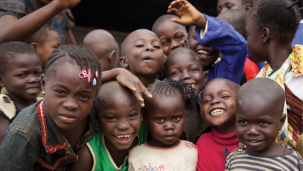 Group of children smile at the camera
