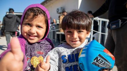 Two children in a refugee camp smiling